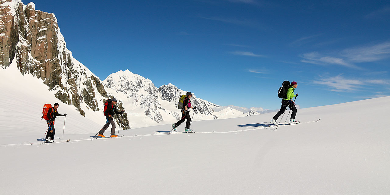 Ski tourers approaching the summit of Mount von Bulow in front of Mount Tasman