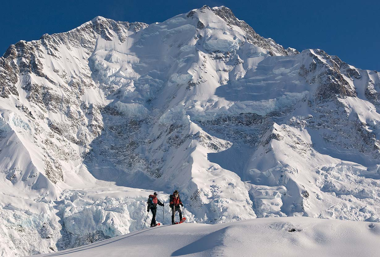 Snowshoers on Ball Ridge, in front of the Caroline Face of Aoraki / Mt. Cook