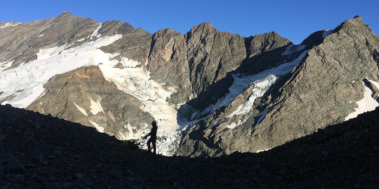 A mountaineer is silhoutted against the Main Divide